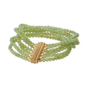 Light green beaded bracelet with multi strands and a gold tone magnetic closure.