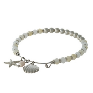 White and silver tone beaded bangle bracelet with sea life charms.