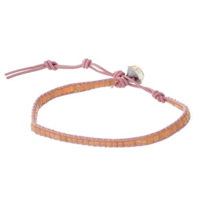 Pink cord bracelet with peach faceted stones and a button closure.