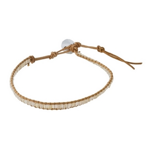 Tan cord bracelet with white faceted stones and a button closure.