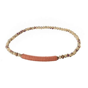 Dainty peach iridescent beaded stretch bracelet with a thread wrap focal.