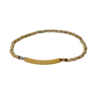 Dainty brown beaded stretch bracelet with a thread wrap focal.