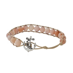Tan cord bracelet featuring peach natural stone beads and a peach tone anchor toggle closure.
