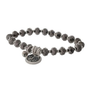 Hematite and silver tone beaded stretch bracelet featuring a circle charm.