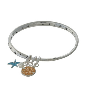 "Silver tone bangle bracelet stamped with ""Life is better at the sea."""