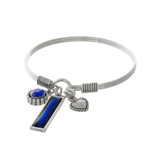Silver tone bangle bracelet with police department themed charms and a hook closure.