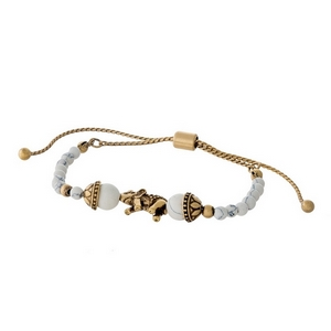 White beaded pull-tie bracelet with a gold tone elephant focal.