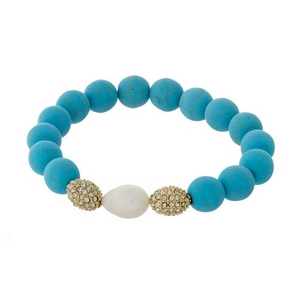 Turquoise natural stone beaded stretch bracelet with a freshwater pearl bead and gold tone accents.