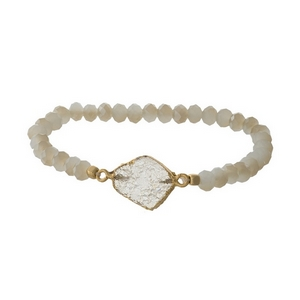 Ivory beaded stretch bracelet with a faux druzy stone and gold tone accents.