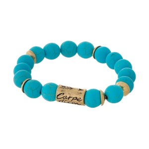 """Turquoise natural stone beaded bracelet with a gold tone bead stamped with """"Carpe Diem."""""""