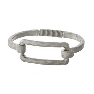 Silver tone bangle bracelet with a spring hinge and an open rectangle shape.