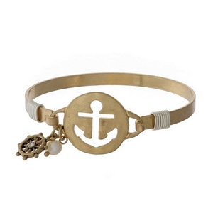 Gold tone bangle bracelet with an anchor cutout.