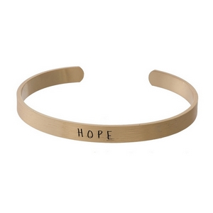 "Gold tone cuff bracelet stamped with ""Hope."""