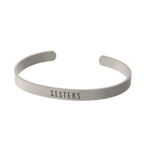 """Silver tone cuff bracelet stamped with """"Sisters."""""""