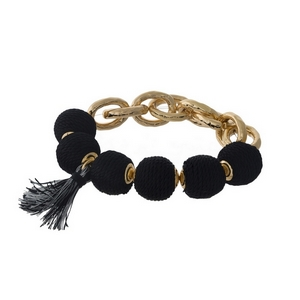 Gold tone stretch bracelet with black thread wrapped ball beads and a tassel accent.
