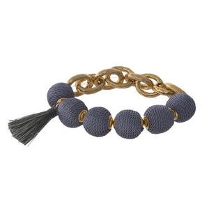 Gold tone stretch bracelet with gray thread wrapped ball beads and a tassel accent.