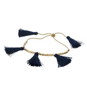 Dainty gold tone pull-tie bracelet with navy blue thread tassels.