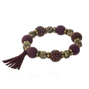 Burgundy thread wrapped and burnished gold tone, stretch bracelet with a tassel accent.