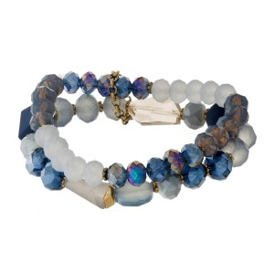 Navy blue, blue and gray beaded, two-row stretch bracelet with a matte finish and gold tone accents.
