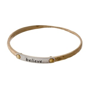 "Gold tone bangle bracelet with a two tone bar, stamped with ""Believe."""