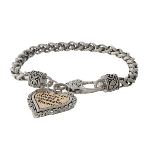 "Silver tone bracelet with a two tone heart charm stamped with ""The love between a Grandma & Granddaughter is forever."""
