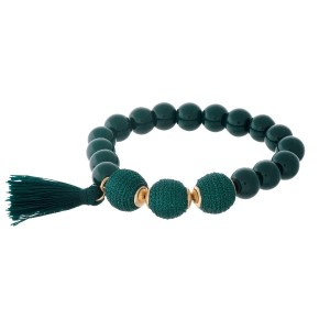Hunter green beaded stretch bracelet with thread wrapped beads and a tassel accent.