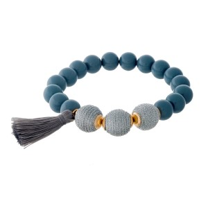 Gray beaded stretch bracelet with thread wrapped beads and a tassel accent.