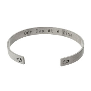 "Metal cuff bracelet stamped with two crosses on the outside and ""One day at a time"" on the inside."