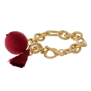 Gold tone toggle bracelet with a thread wrapped bead and tassel accent.