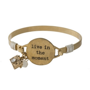 """Metal bangle bracelet with a circle focal stamped with """"live in the moment."""""""