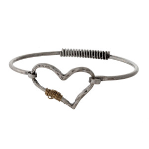 Metal bangle bracelet with an open heart focal and wire wrapping accents.