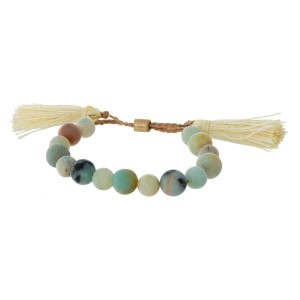 Natural stone beaded pull-tie bracelet with tassels on the ends.