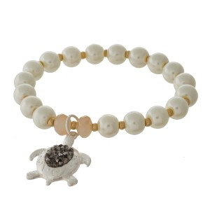 Pearl and peach beaded stretch bracelet with a turtle charm.