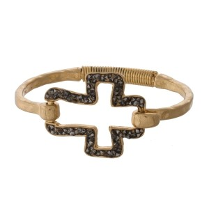 Burnished metal bangle bracelet with a crushed hematite cross focal and a latch closure.