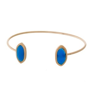 Dainty gold tone, metal cuff bracelet with faceted stones at the openings.