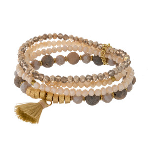 Four row, beaded stretch bracelet with gold tone accent, natural stones and a tassel charm.