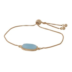 Dainty gold tone bracelet with a faceted stone focal and a pull-tie closure.