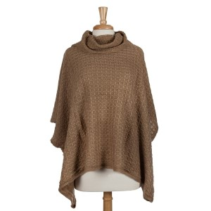 Beige short sleeve, turtle neck poncho top with a cable knit pattern. 100% acrylic. One size fits most.