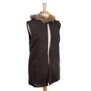 Charcoal vest with a raccoon fur trimmed hood, a front hook closure and pockets. 68% acrylic, 15% polyester, 17% spandex. One size fits most.