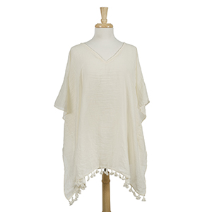 Lightweight, ivory, poncho with tassels. 100% viscose. One size fits most.