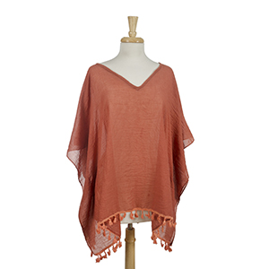 Lightweight, rust orange, poncho with tassels. 100% viscose. One size fits most.