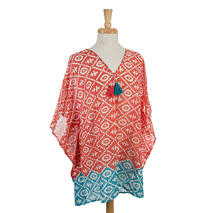 Lightweight coral and white printed poncho with tassel accents. 100% cotton. One size fits most and can also be worn as a swimsuit cover up.