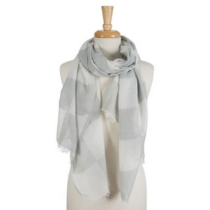"White open scarf featuring a gray gingham print and frayed edges. 40% cotton and 60% polyester. Approximately 28"" x 78"" in size."