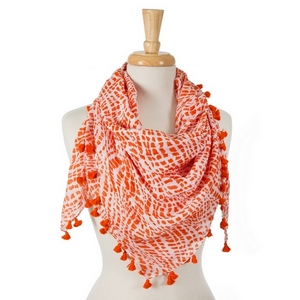 "Orange and white tie-dye print square scarf with pom poms along the edges. 100% cotton. Measures approximately 42"" x 42"" in size."