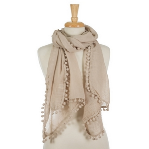 "Beige open scarf with pom poms on the edges. 35% viscose and 65% polyester. Measures approximately 72"" x 28"" in size."