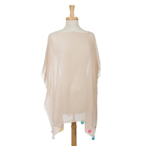 Beige short sleeve poncho with multicolored pom poms on the bottom hem. 30% cotton and 70% polyester. One size fits most.