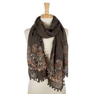 """Charcoal gray, lightweight scarf with floral embroidery and pom poms on the outer trim. 65% polyester and 35% viscose. Measures 26"""" x 70"""" in size."""