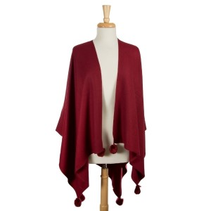 Burgundy cape with pom pom accents. 100% acrylic. One size fits most.
