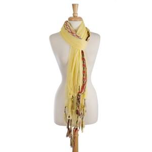 "Lightweight, solid scarf with an aztec print along the edge and tassel accents. 100% viscose. Measures 28"" x 80"" is size."