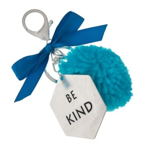 """Silver tone key chain or bag charm stamped with """"Be Kind"""" and a blue pom pom. Approximately 5.5"""" in length."""